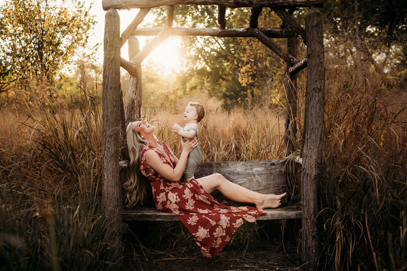 Family Photographer, sitting on a wooden bench in the forest, a mother holds up her toddler son, both smiling