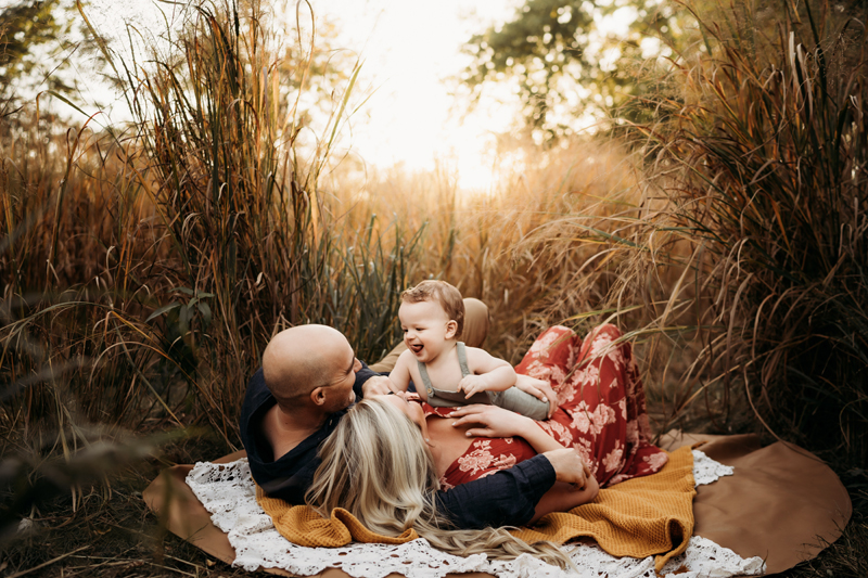 Family Photographer, a man and woman lay in the grass on a blanket, their smiling baby son perched atop of them