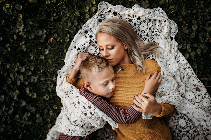 Family Photographer, a mother holds her toddler son close on a quilted blanket in the grass
