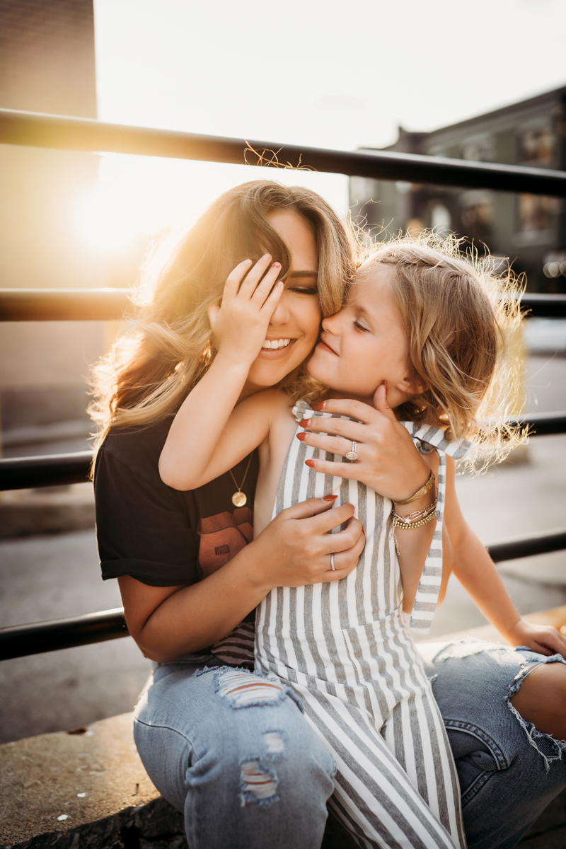 Family Photographer, in an urban environment, mom sits along a concrete wall, her daughter squeezes her face close, they both smile