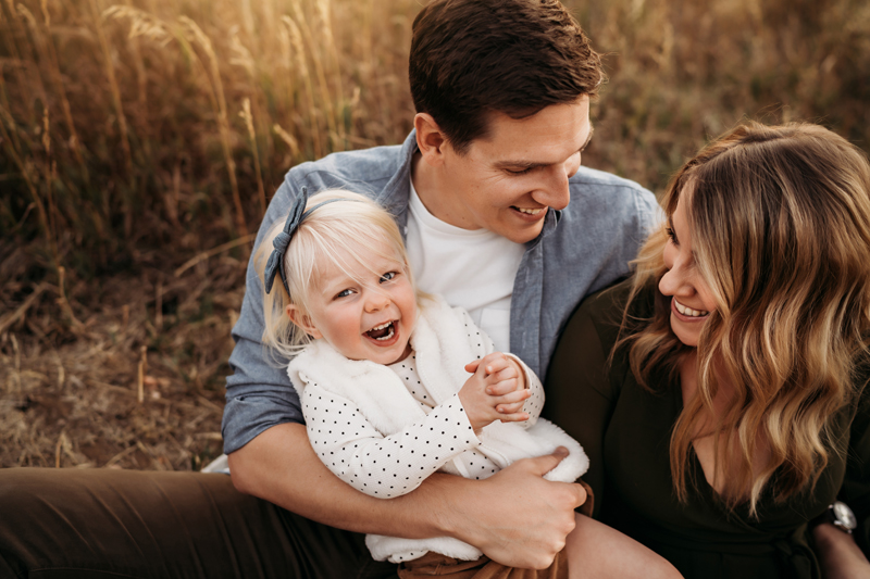 Family Photographer, young dad gazes at mom as she gazes as their laughing daughter being held by dad