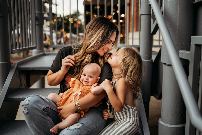 Family Photographer, On a city playground, mom sits holding baby and smiling at their toddler face to face