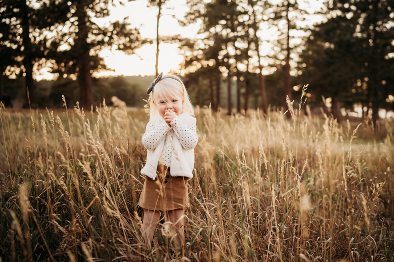 Family Photographer, a toddler girl dressed in a fleece vest, stands in a field happily