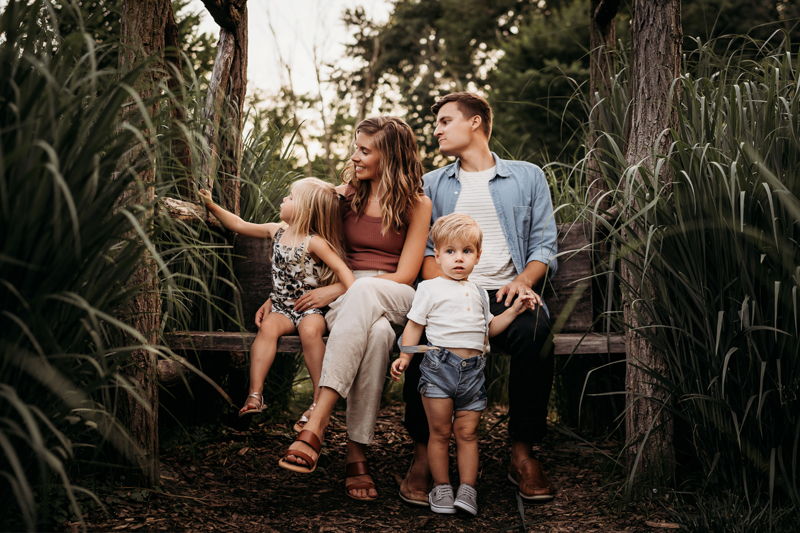 Family Photographer, on a wooden bench, a young father and mother sit closely watching their daughter reach for plants, their son stands before them looking off