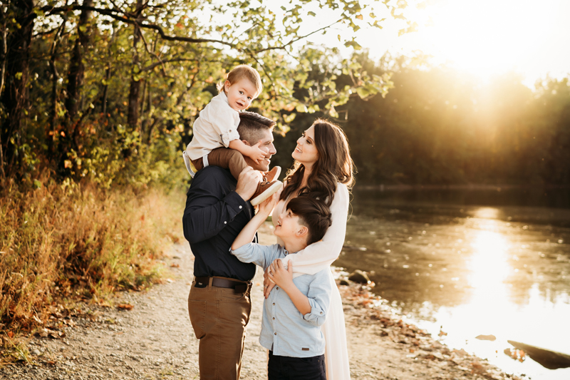 Family Photographer, a father looks at his wife, he carries a son on his shoulders and another son is wrapped in mothers arms