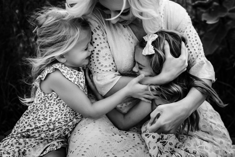 Family Photographer, a mother squeezes one her daughters as the other daughter squeezes mom tight, they're all laughing