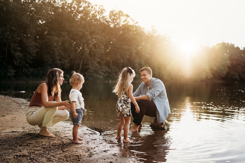 Family Photographer, Dad and Mom crouch at lakeshore with their toddler son and daughter