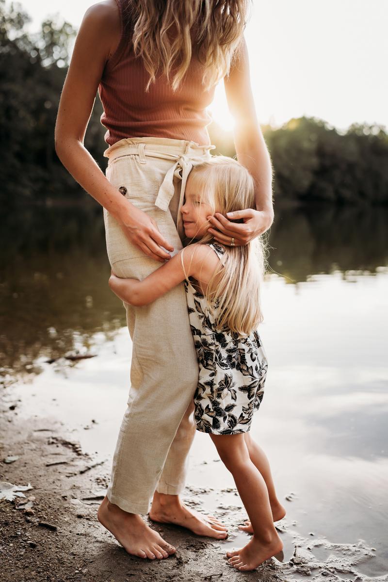 Family Photographer, toddler girl hugs moms legs tight near a lakeshore