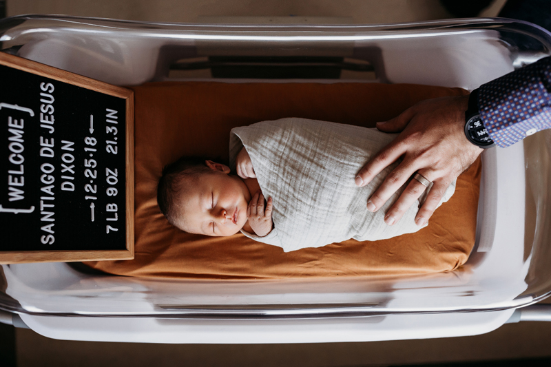 Fresh 48 Photography, a baby lays asleep in a hospital crib, dad hand is on her for comfort