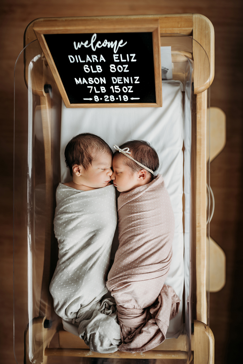Fresh 48 Photography, two babies lay in a hospital crib face to face, one in a baby blue blanket, one in a soft pink