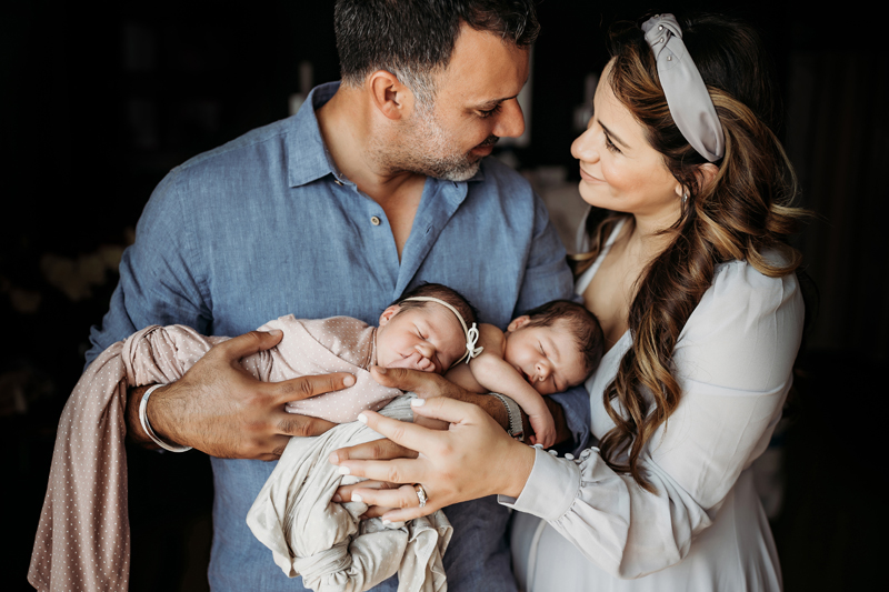 Fresh 48 Photography, man and woman gaze into each other's eyes happily while holding their newborn twins