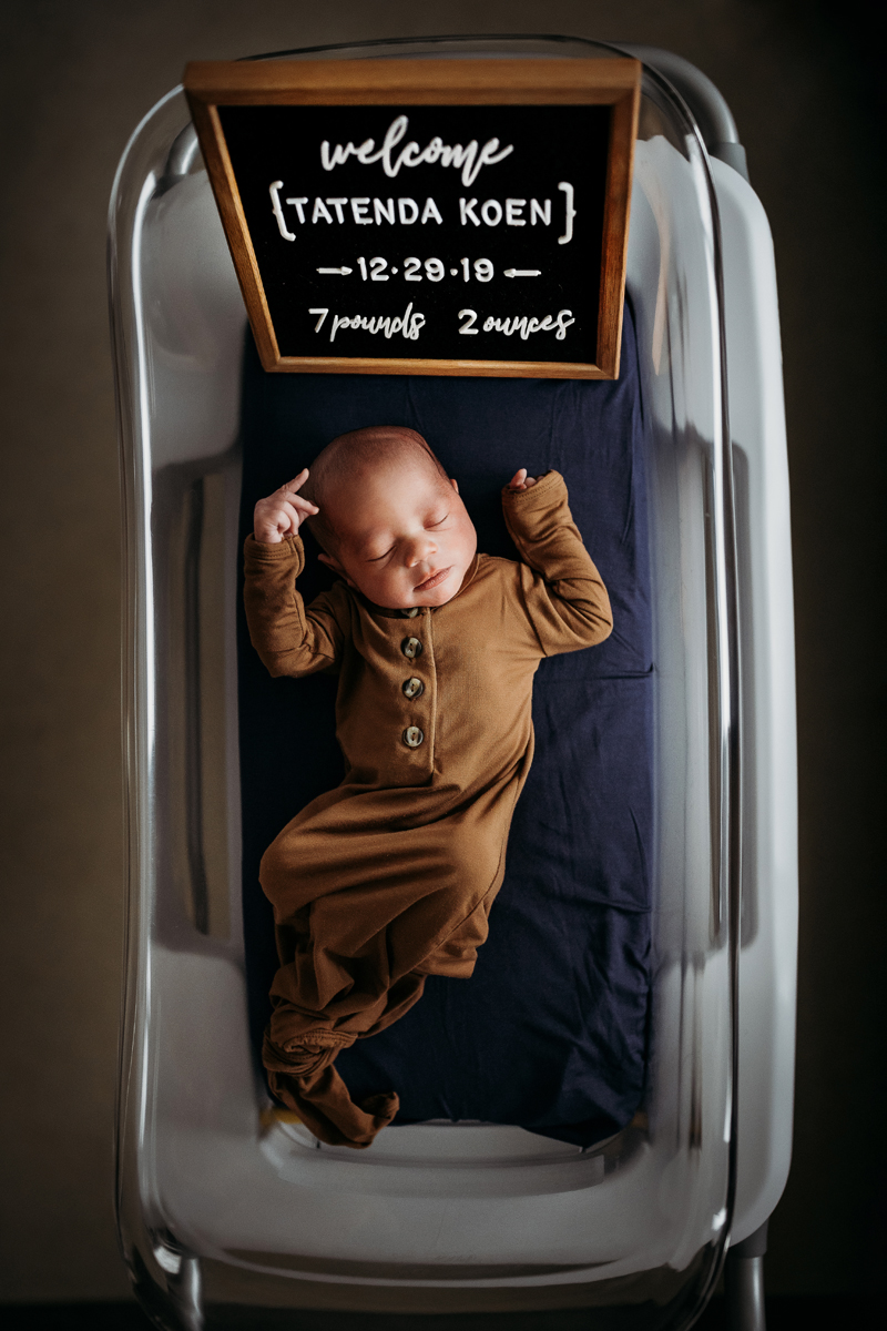 """Fresh 48 Photography, a baby boy lays in a hospital bed with a sign that reads """"welcome Tatenda, 7 lbs 2 oz"""""""