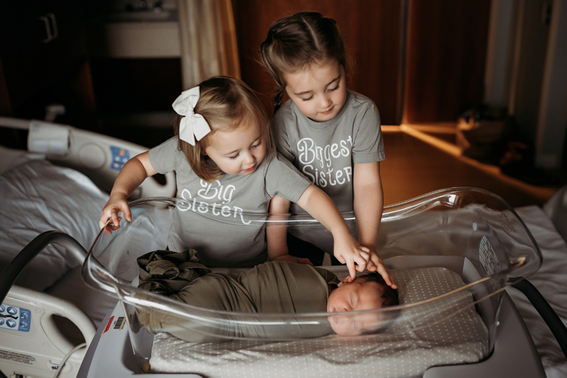 Fresh 48 Photography, baby lays in hospital bassinet, two toddler sisters reach over to say hello