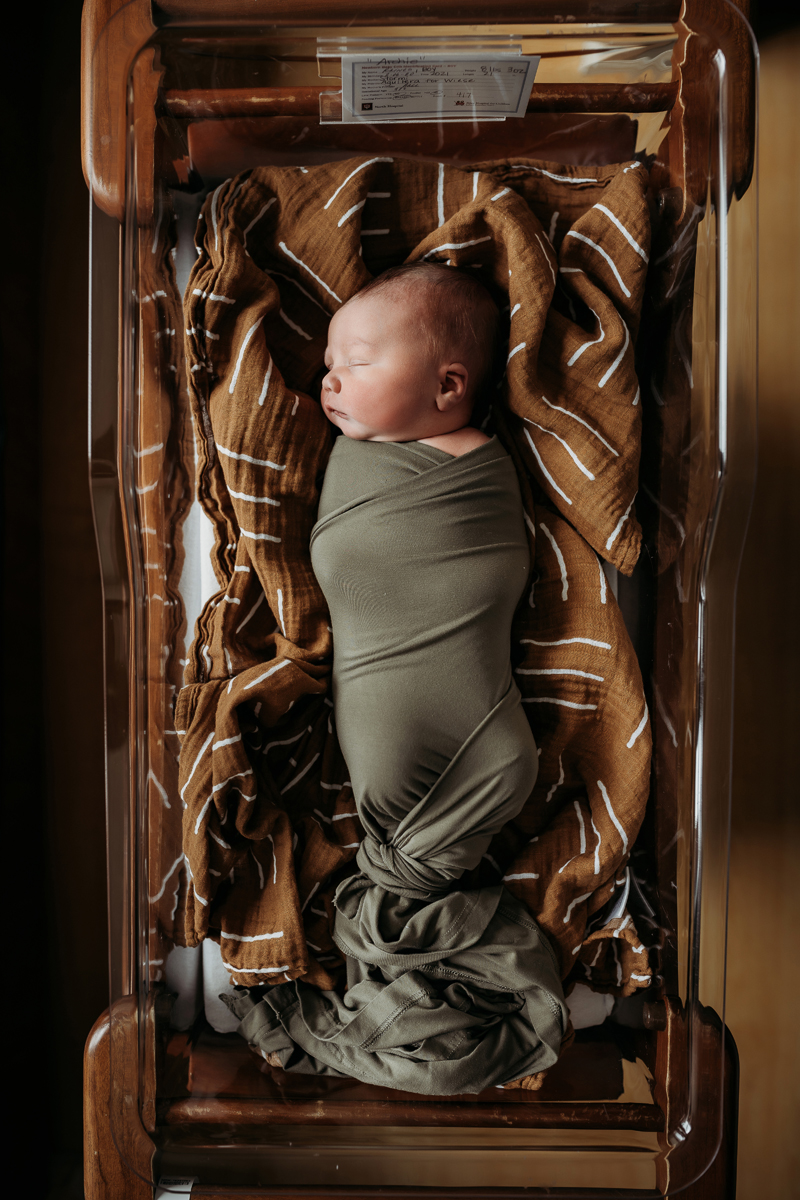 Fresh 48 Photography, baby in wood hospital bassinet sleeps wrapped in a blanket