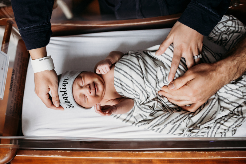 Fresh 48 Photography, a baby with a grin on face lays in a hospital bassinet, parents hands hold onto him. his beanie reads Sebastian