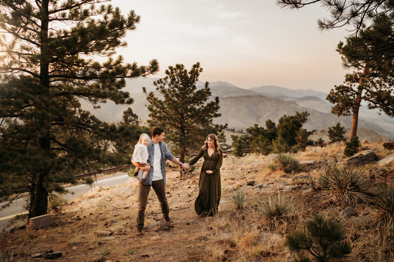 Maternity Photography, a man holding his young daughter leads his expecting wife up a hillside