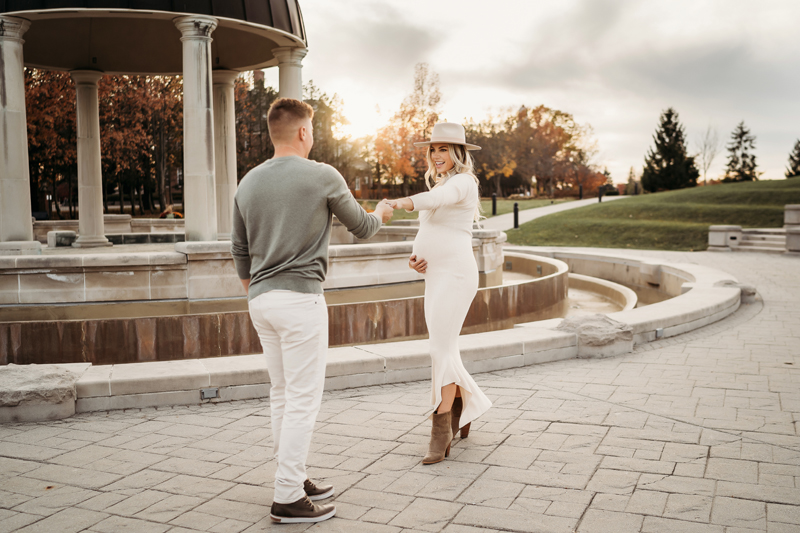 Maternity Photography, a man and an expecting woman dance near a fountain promenade at the parkrk
