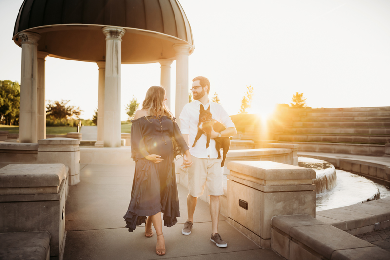 Maternity Photography, in an outdoor amphitheater a man and expecting woman walk hand in hand, the man holds their small french bull dog