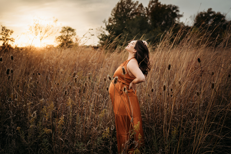 Maternity Photography, an expecting mother enjoys the breeze at sunset in a grassy field