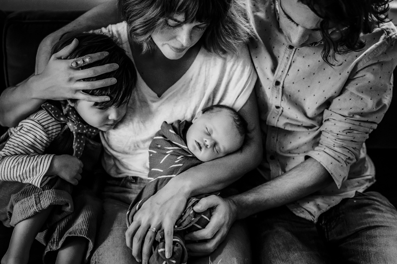 Newborn Photography, Young Mom and Dad hold a toddler and their newborn baby in their arms