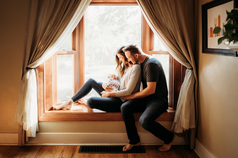 Newborn Photography, In a window nook, a woman reclines into her husbands arms, she holds their new baby