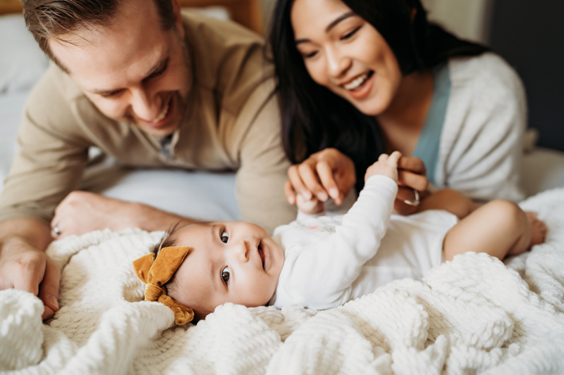 Newborn Photography, A baby lays on blankets smiling as mom and dad admire her also smiling