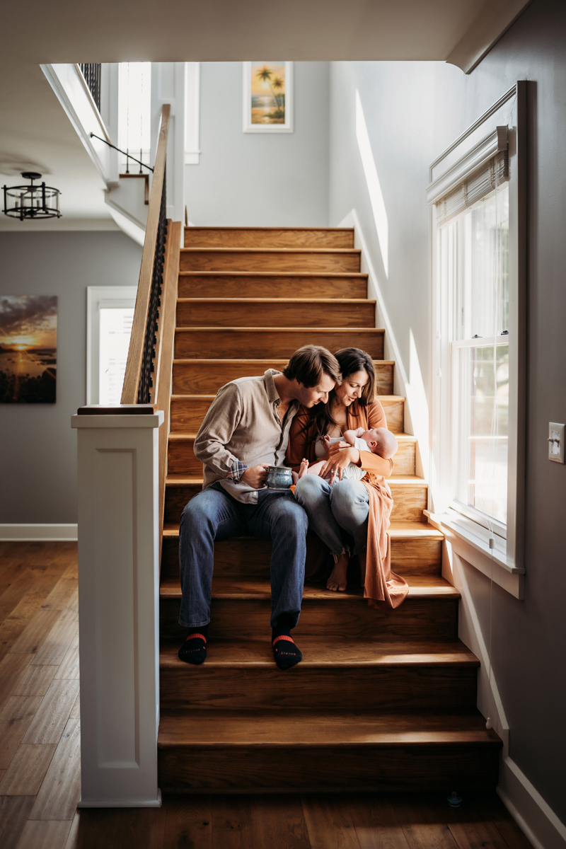 Newborn Photography, Mother and Father sit in the stairs in their home gazing at their baby