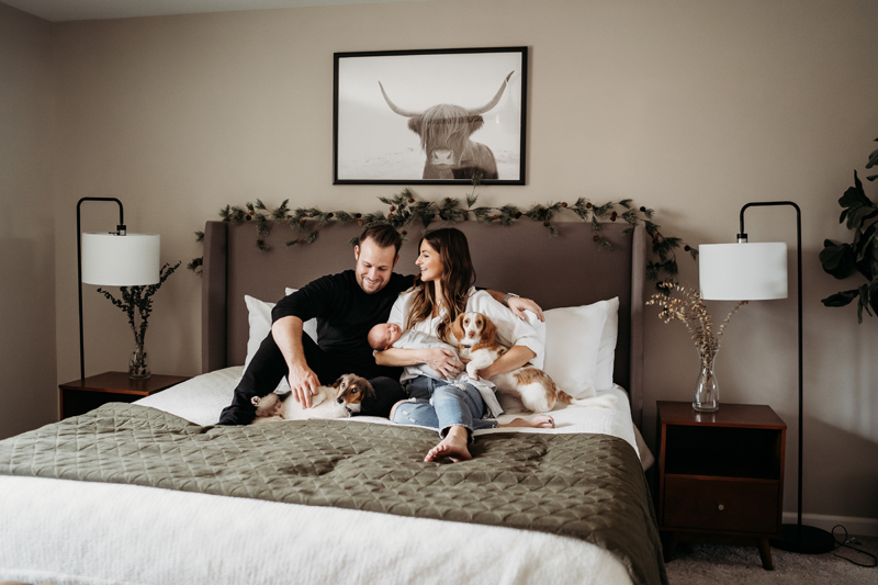 Newborn Photography, man and woman sit in their bedroom smiling, mom holds newborn baby in one hand and dog in the other