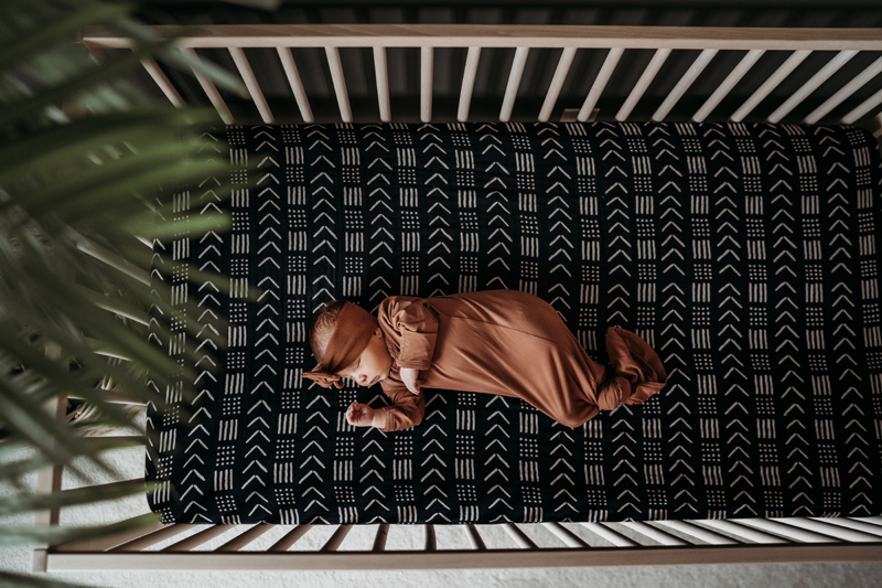 Newborn Photography, a baby lays in a crib asleep, the sheets have chevron patterns