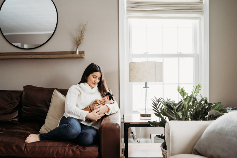 Newborn Photography, mom sits in clean living room holding newborn baby daughter