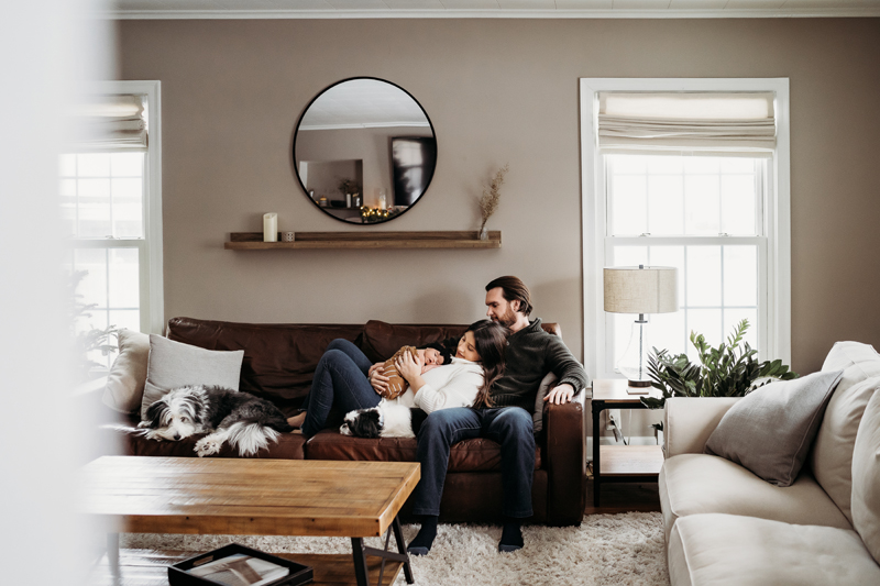Newborn Photography, Woman reclines on Man on the couch in living room, she holds their newborn baby