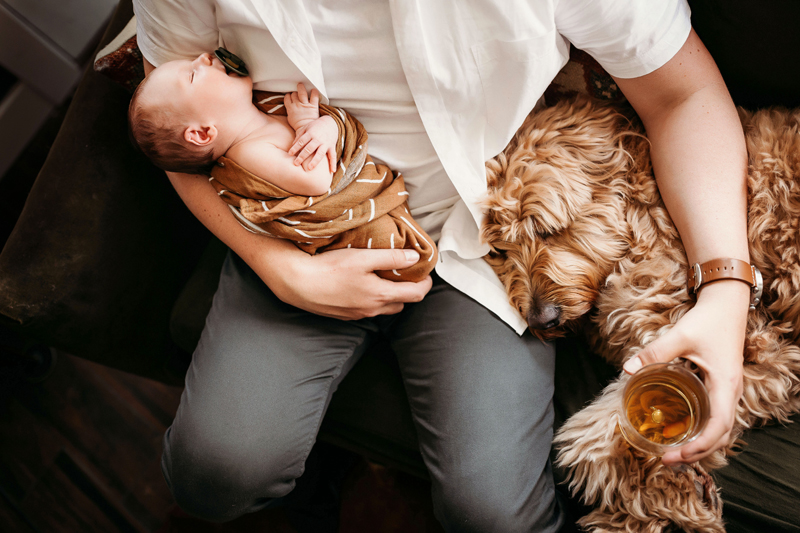 Newborn Photography, Dad in casual business dress holds newborn baby and a drink in another hand being propped by their dog